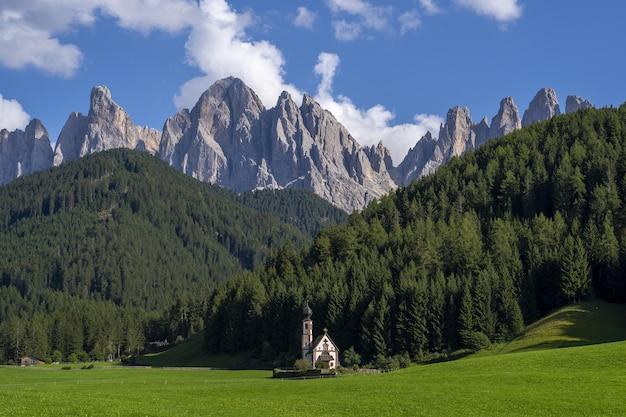 Chiesa in un paesaggio verde circondato da montagne rocciose in val di funes, st. italia Foto Gratuite