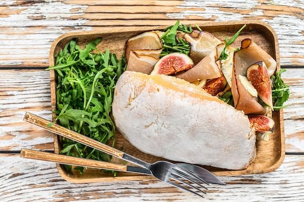 ルッコラ、イチジク、生ハム、ブルーチーズのチャバタサンドイッチ Premium写真