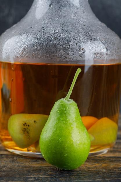 木製のテーブルの上にボトルに梨とサイダードリンク 無料写真