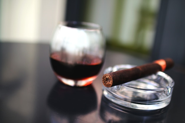 Cigar with a glass of alcohol on a black table Free Photo