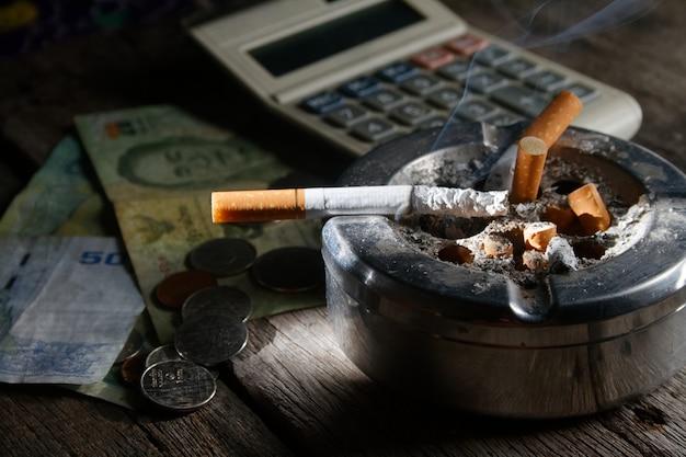 Cigarette and calculator with mone Premium Photo