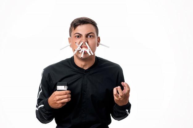 Сигареты есть везде. молодой человек с гневом к курению. на его лице сигареты повсюду - в носу, во рту, в ушах. курение убивает. он сжимает кулак в гневе. изолированные Premium Фотографии