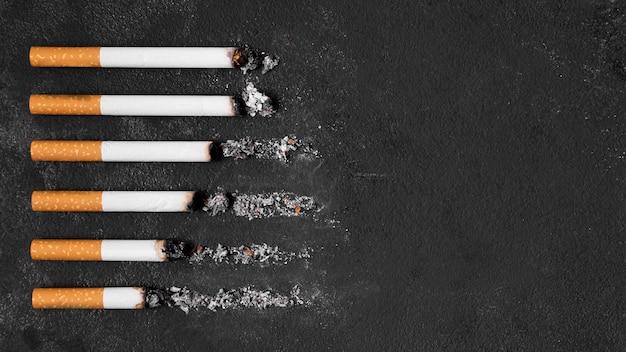 Cigarettes arrangement on black background Premium Photo