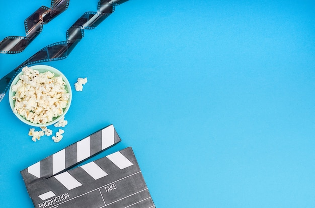 Cinema concept - clapperboard with popcorn and film strip on blue background with copy space. Premium Photo