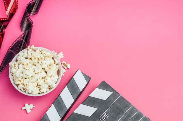 Cinema concept - clapperboard with popcorn and film strip on pink background with copy space. Premium Photo