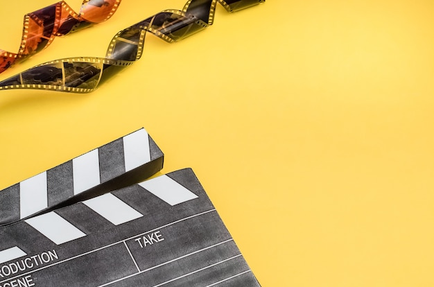 Cinema concept - clapperboard with popcorn and film strip on yellow background with copy space. Premium Photo
