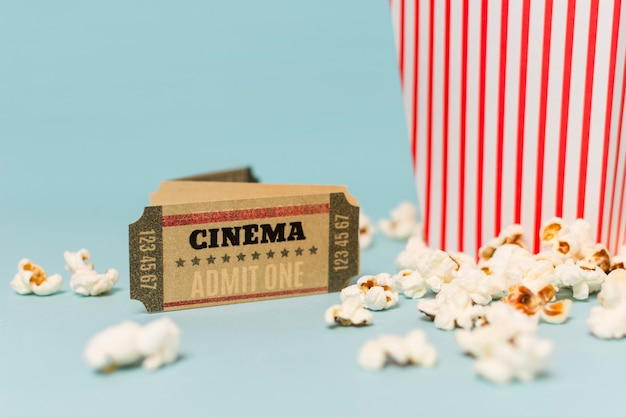 Cinema ticket near the popcorns against blue background Free Photo