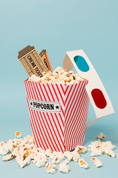 Cinema tickets and 3d glasses on popcorn box against blue background Free Photo