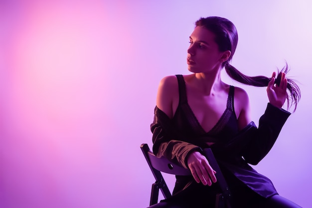 Cinematic night portrait of woman in neon. beautiful young woman in a stylish clothes posing on chair  in colorful lights. Premium Photo