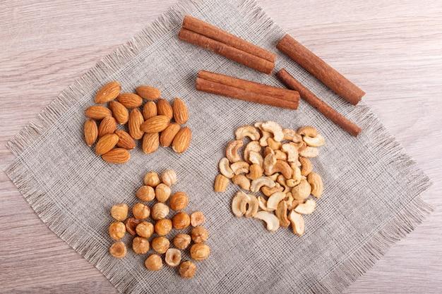 Cinnamon, almonds, hazelnuts, cashew on a linen napkin. Premium Photo