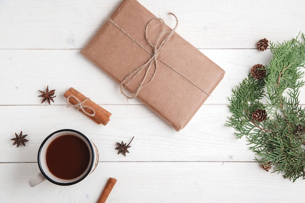 Cinnamon,anise stars,fir branches,a cup of hot chocolate and a box with a gift Premium Photo