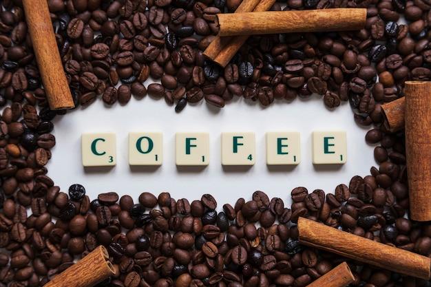 Cannella e chicchi di caffè intorno alla scrittura Foto Gratuite
