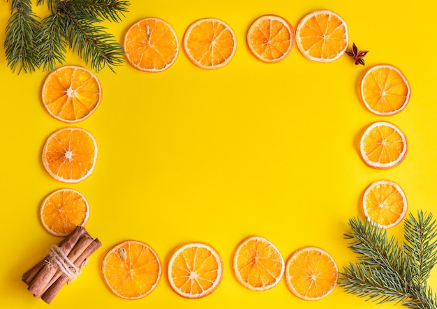 Cinnamon, fir branches, dried orange fruit slice and anise on a yellow paper frame. Premium Photo