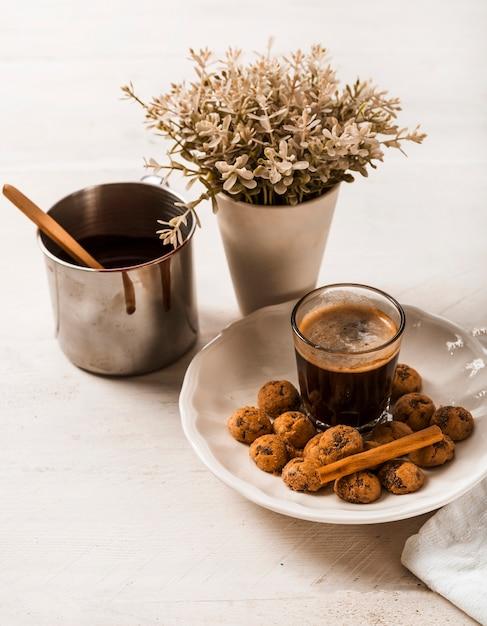 Cinnamon sticks on chocolate cookies with coffee glass and vase Free Photo