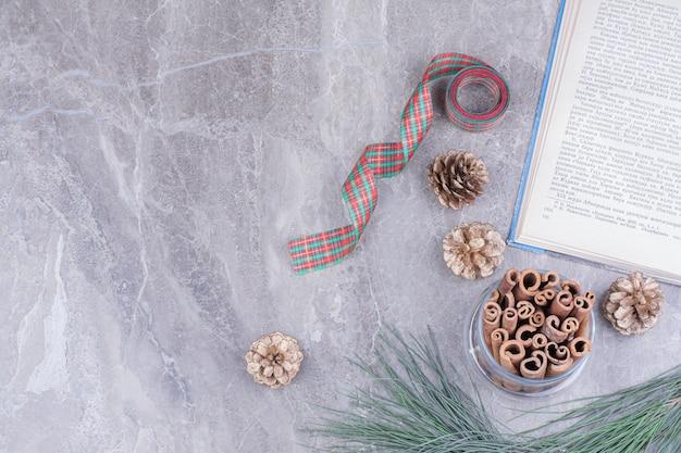 Bastoncini di cannella in un barattolo di vetro con coni di albero di remo intorno. Foto Gratuite