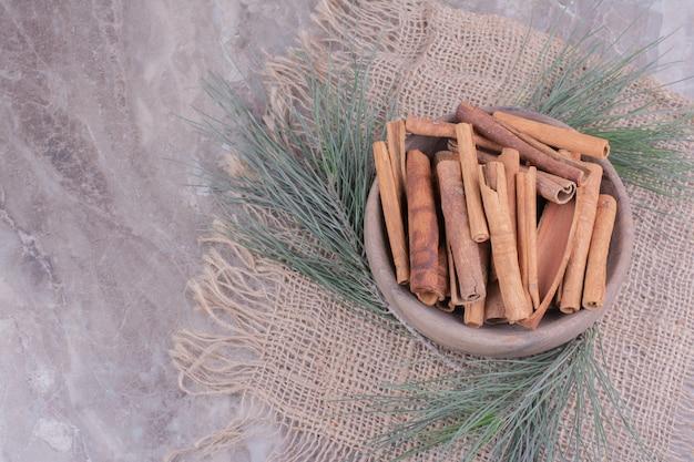 シナモンは樫の木の枝が周りにある木製のカップに固執します 無料写真