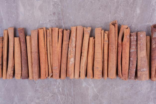 Bastoncini di cannella in fila sulla superficie della pietra Foto Gratuite