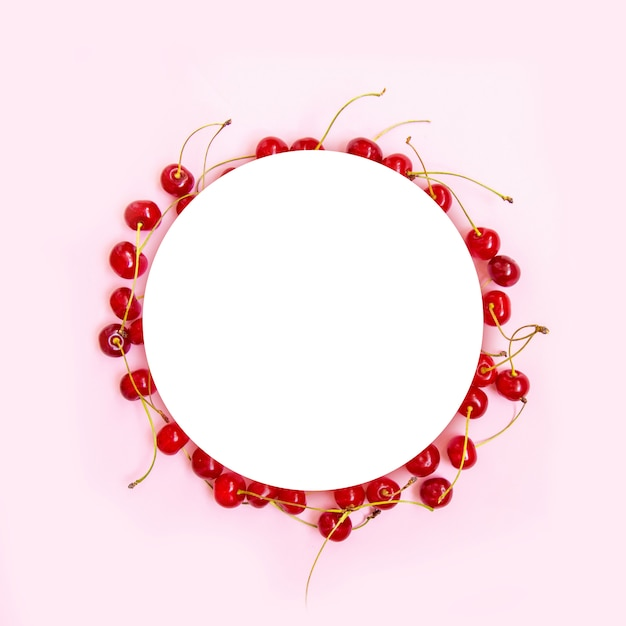 Circle frame of red ripe cherries with green mint leaves on a pink background Premium Photo