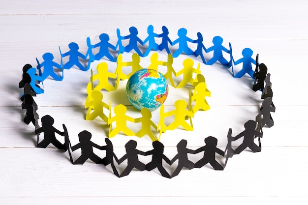 Circle of paper people holding hands around the globe made of paper cut Premium Photo