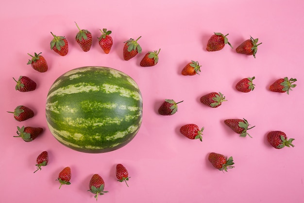 Circle of strawberries teamwork on pink background and a watermelon Premium Photo