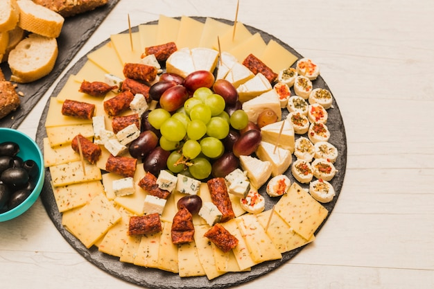 Circular black slate with cheese platter; grapes and smoked sausages on wooden table Free Photo