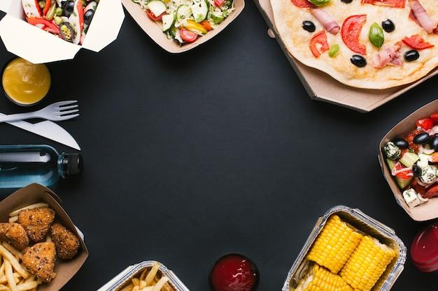 Circular food frame with pizza, salad and corn Premium Photo
