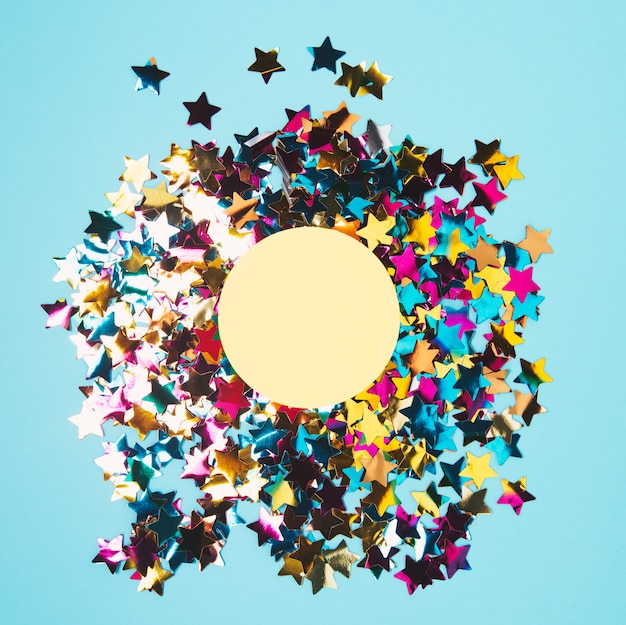 Circular frame over the colorful star shape confetti against blue background Free Photo
