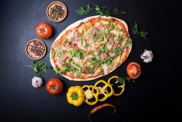 Circular frame made of fresh ingredients around delicious italian pizza over black counter Free Photo