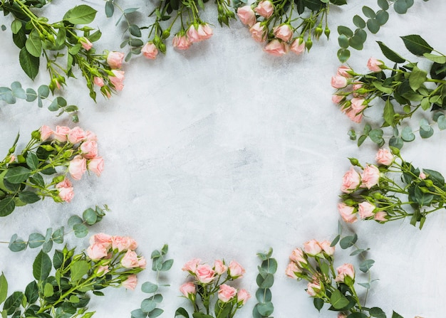 Circular frame made with bunch of roses on concrete background Free Photo