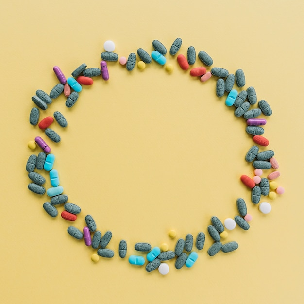 Circular frame made with colorful pills on yellow background Free Photo