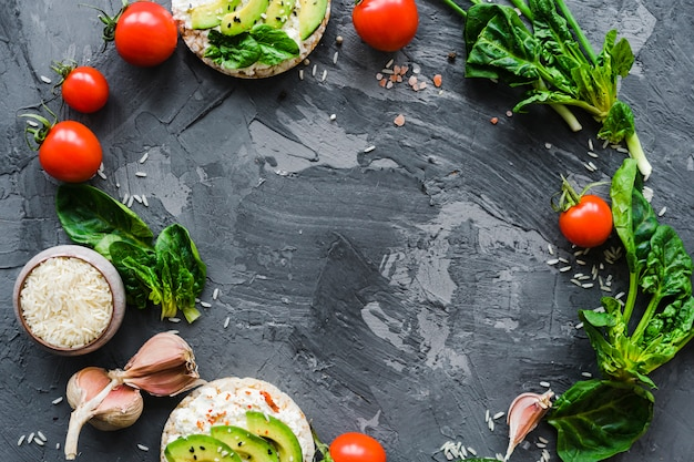 Circular frame made with fresh vegetables and healthy snack over weathered cement wallpaper Free Photo