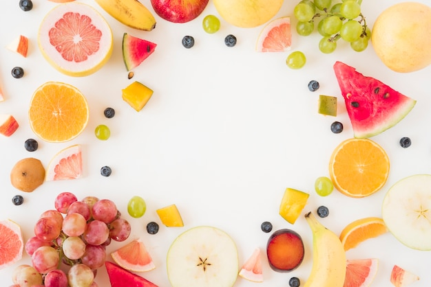 Circular frame made with many organic fruits on white backdrop Free Photo