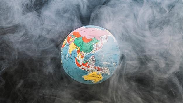 Circular globe surrounded by smoke