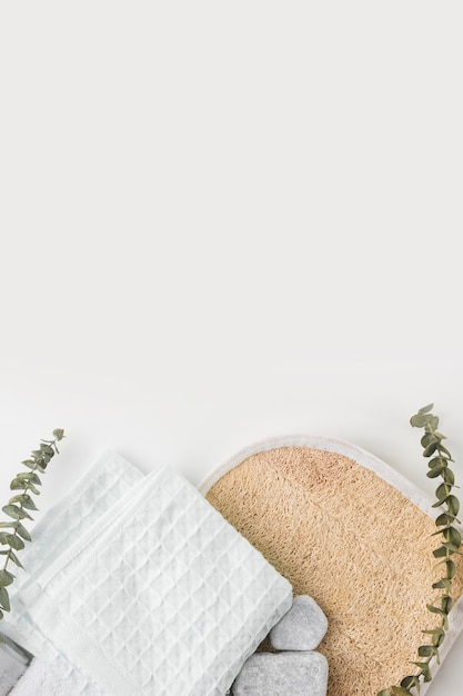 Circular loofah body scrubber; cotton napkin and spa stones with twigs isolated on white background Free Photo