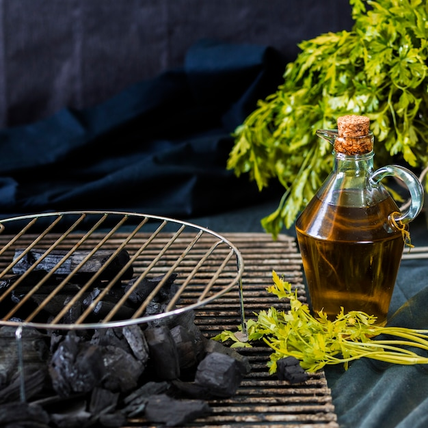 Circular metal sheet on coal with oil bottle and coriander over the table Free Photo