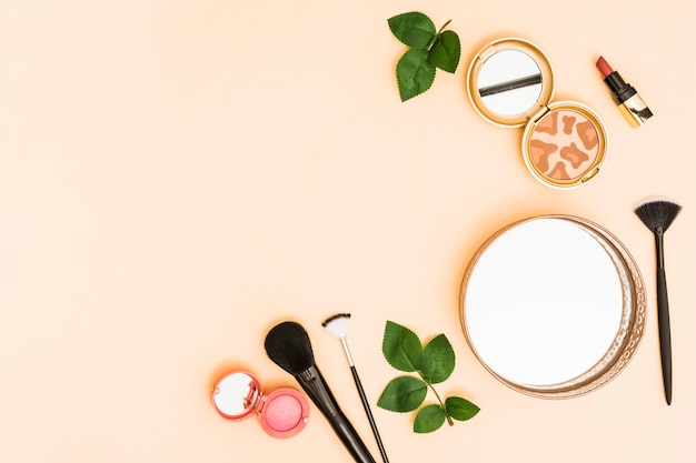 Circular mirror; compact powder; lipstick and makeup brushes with leaves on pastel background Free Photo