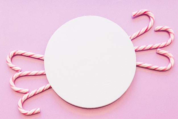 Circular white blank frame with xmas candy canes design on pink background Free Photo