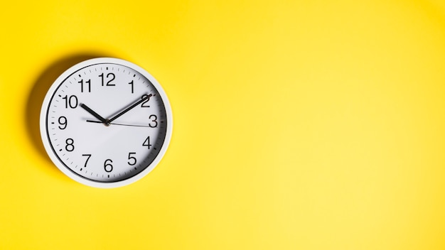 Circular white clock on yellow wall background Free Photo