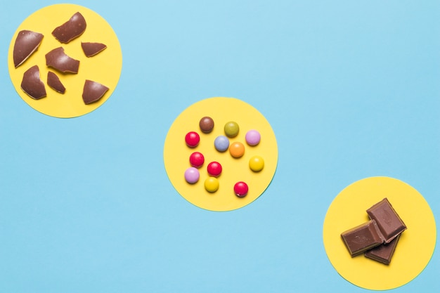 Circular yellow frame over the colorful gem candies; easter egg shells and chocolate pieces on blue background Free Photo