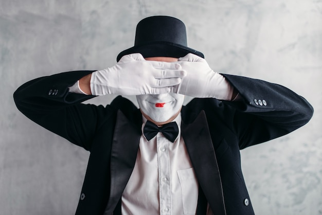 Circus artist posing, pantomime with white makeup mask. comedy actor in suit, gloves and hat Premium Photo