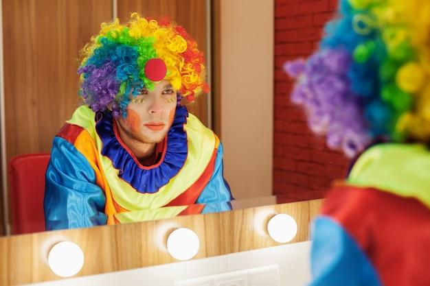 Circus clown looks in a mirror in makeup room. Premium Photo