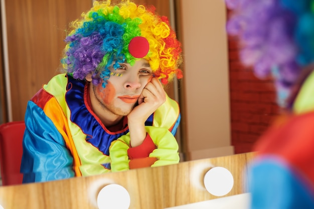 Circus clown looks in a mirror in makeup room. Premium Photo