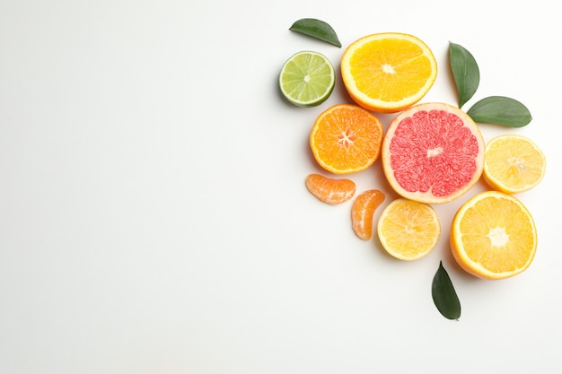 Citrus fruits and leaves on white background, space for text Premium Photo