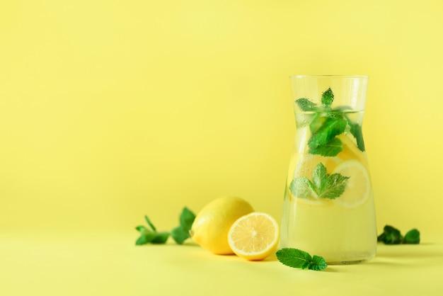Citrus lemonade - cold water with ice, mint, lemon on yellow background. detox drink. Premium Photo