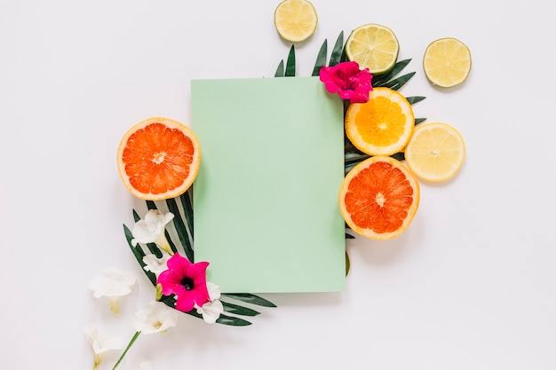 Citruses and flowers near paper sheet on leaf Free Photo