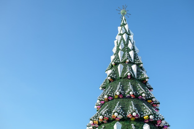 City christmas tree against a blue sky. christmas garlands. weekends and holidays Premium Photo