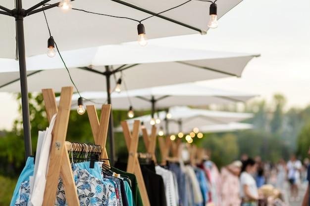 Городская ярмарка. оформление мероприятия. белые зонтики, на которых висят лампочки Premium Фотографии