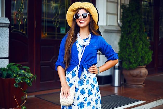 通りで楽しんで一人で歩いている幸せなかわいい女の子、夕方の日光、レトロなドレスのヴィンテージ帽子、幸せなポジティブな気分の都市ライフスタイルファッションの肖像画。 無料写真