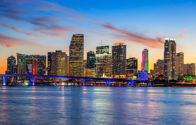 Город майами флорида, панорама летнего заката с красочными освещенными деловыми и жилыми зданиями и мостом на заливе бискейн Premium Фотографии