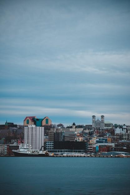 Skyline della città sotto il cielo nuvoloso grigio durante il giorno Foto Gratuite